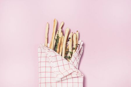 Homemade Cheese or Bread Sticks with Herds Crispy Bread Sticks with Thyme and Rosemary on Pink Background Top View Horizontal