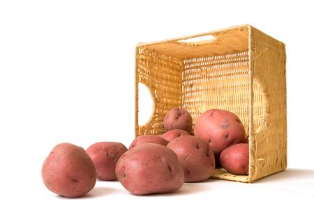 Red baking potatos out of a wicker basket.