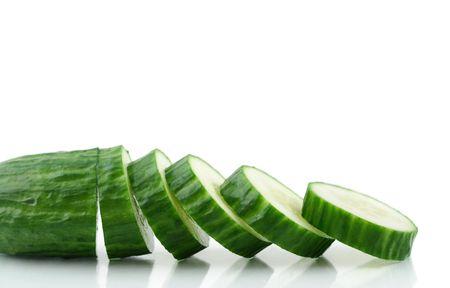 progressively: A Cucumber progressively sliced - white background.