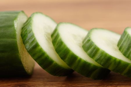 cuke: Sliced cucumber on a wooden cutting board.