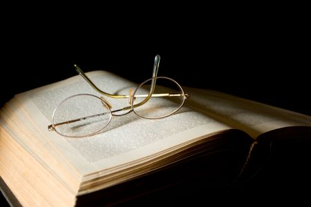 bind: Glasses Lying on Book - text blurred slightly to prevent any copyright issues. Stock Photo
