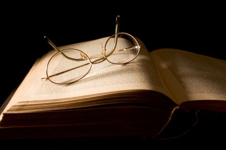 Glasses Lying on Book - text blurred slightly to skirt copyright problems. photo