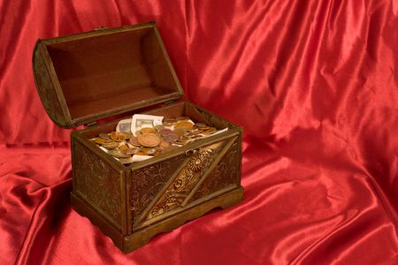 Treasure Chest on Red Satin Background, With Coins Фото со стока