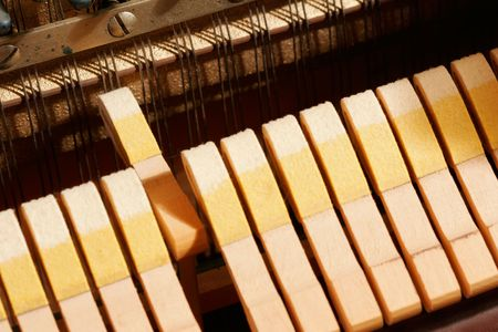 insides: A hammer striking the strings inside a piano. Stock Photo