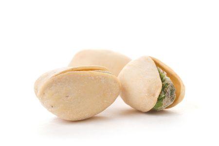 Three pistachios on a white background.