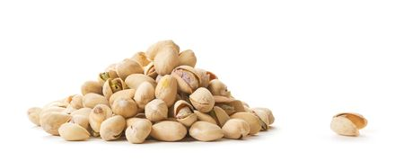 A pile of Pistachios on white.  (A pile of pistachios sitting next to one empty shell.) photo