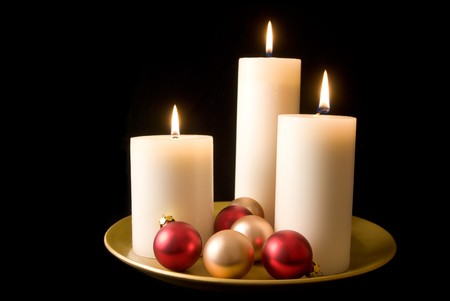 Three candles and red and gold ornaments on a decorative gold plate. photo