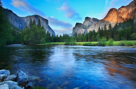 El Capitan and the Cathedral Rocks (with Bridalviel Falls) seen from the Merced River at dusk.
