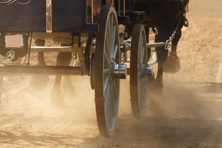 A wagon being pulled by draft horses through a dusty field.