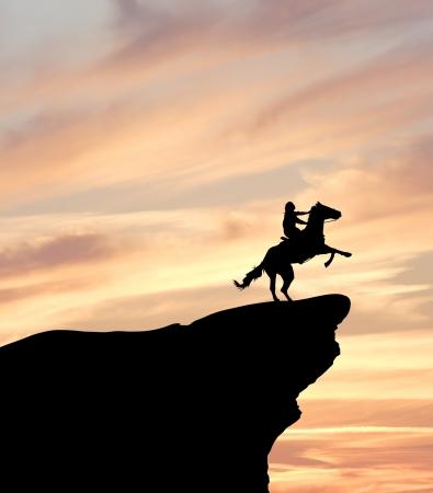 uomo a cavallo: Silhouette di un cavaliere su una scogliera al tramonto