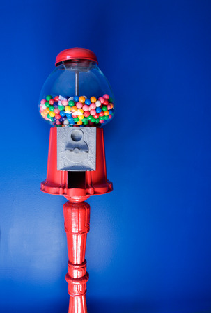 An old fashioned gumball machine against a colorful blue background, vertical  photo