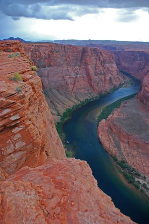 Stunning Colorado River Snaking Through Steep Red Cliffs with Stormclouds photo