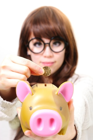 hand putting coins into a piggy bank Stock Photo - 12720768