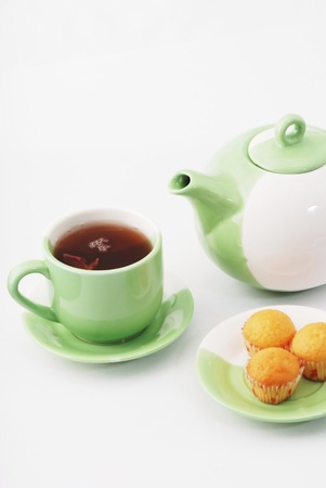Tea being poured into tea cup isolated on a white background Stock Photo