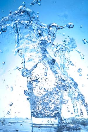 vaso con agua: Salpicaduras de agua de vidrio