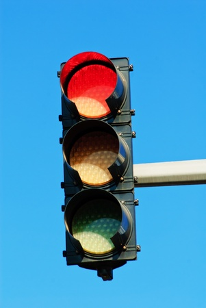 Red traffic light against a bright blue sky photo