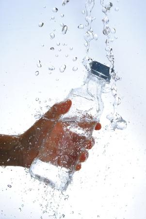 Water bottle in hand, in a spray of water droplets Standard-Bild