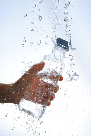 Water bottle in hand, in a spray of water droplets Stock Photo