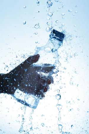welling: Bottiglia d'acqua in mano, in uno spruzzo di goccioline d'acqua