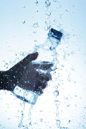 welling: Water bottle in hand, in a spray of water droplets Stock Photo