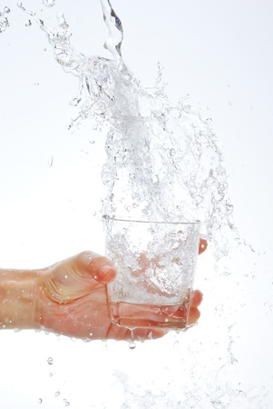 Water bottle in hand, in a spray of water droplets photo