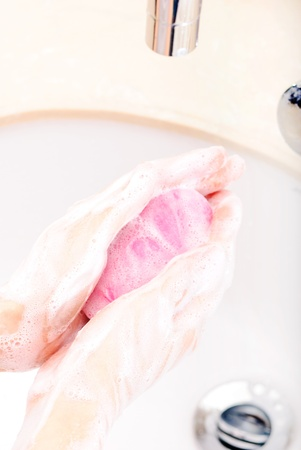 hands covered with soap being washed in the sink photo