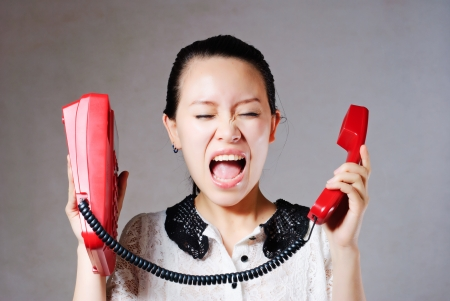 Young angry woman yelling on phone photo