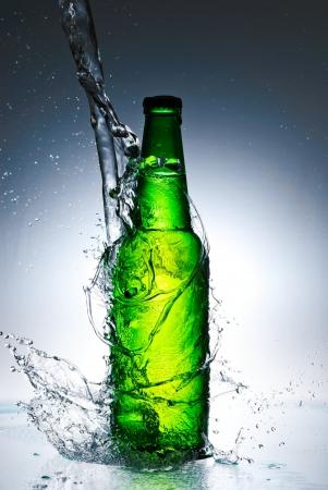 Beer bottle with water splash photo