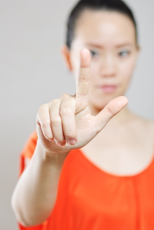 Businesswoman touching and imaginary screen with her finger - isolated