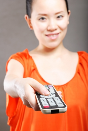 Young women with a remote control Stock Photo - 13875106