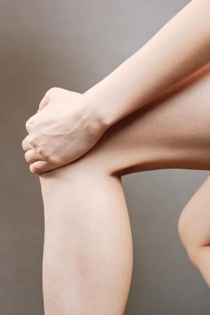 Leg Injury. Woman holding on sore knee.