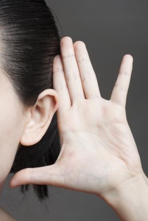 oir: Mujer joven escuchando de cerca.