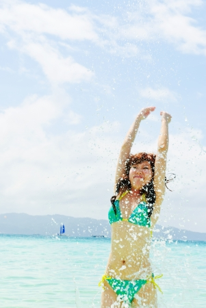beautiful young woman in bikini bathing and splashing happily in the sea at the resort photo