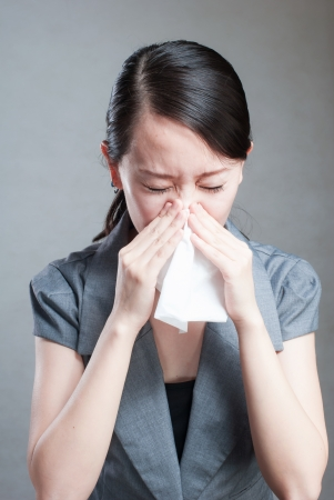 young woman has a cold and holding a tissue