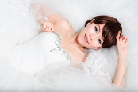 bride sitting in wedding dress, studio shot photo