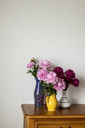 Three jugs with Pink and dark pink Peony standing in a yellow, blue and black and white jug on dark brown oak tabletop