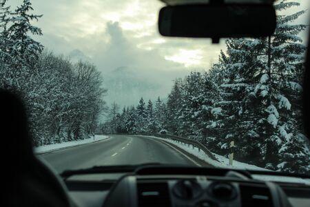 Road trip in the car driving through snowy mountains in Tirol, Austria Imagens