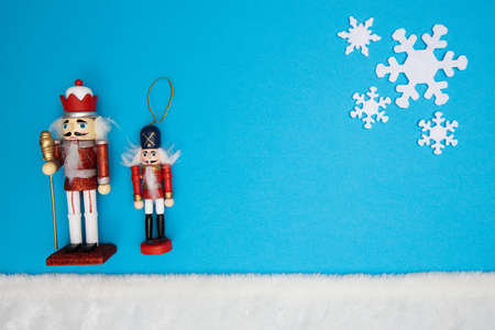 Nutcrackers on blue background with white snowflakes and white fur as snow