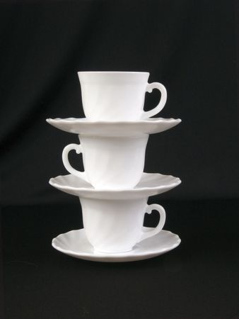 A stack of cups and saucers on the black background photo