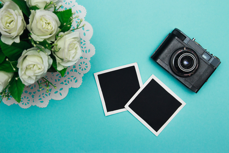 blanks: vintage retro camera on wooden table background with blanks photo to placed your pictures, bouquet of pink roses, gift boxes and heart made from film. valentines day background. top view