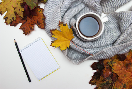 Top view of Cup of black coffee with autumn leaves, a warm scarf on white background