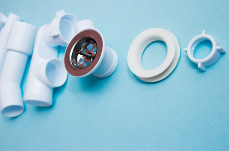 White plastic fittings for plumbing on a blue background