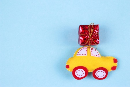 holiday concept with gift boxes on toy cars on blue background
