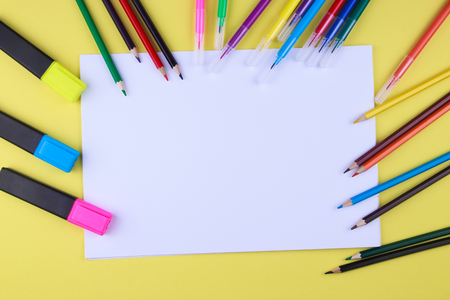 White sheet of paper on a yellow background with copy space and place to inscribe around a color pen ink painters, brushes and pencils copy space. Brash is paint a red color paint. top view