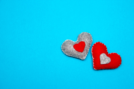 Two red felt handmade hearts on a blue background. Top view. Stock Photo