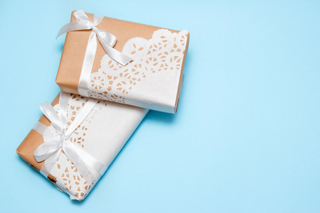 Gifts of craft paper decorated with a lace napkin on a blue background with copy space. Top view.