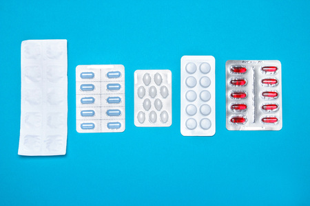 Capsule pills in a blister pack, on a blue isolated background. The concept of global health. Antibiotics, drug resistance. Antimicrobial capsule tablets. Pharmaceutical Industry for Pain.