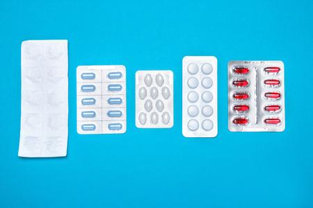 Píldoras de la cápsula en un blister, sobre un fondo azul aislado. El concepto de salud global. Antibióticos, farmacorresistencia. Tabletas de cápsulas antimicrobianas. Industria farmacéutica para el dolor.