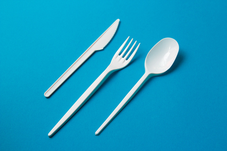 Plastic Fork, Spoon and Knive on Blue Background.