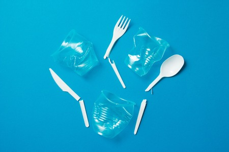 White broken single-use plastic knives, spoons, forks and plastic drink straws on a blue background. Say no to single use plastic. Environmental, pollution concept Stock Photo